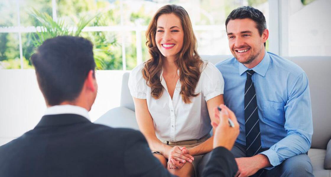 casal conversando com um corretor imobiliário sobre as vantagens de comprar um imóvel na planta